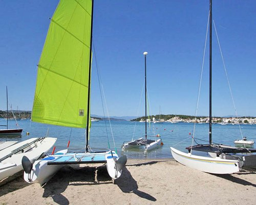 Sailboats parked on the beach.