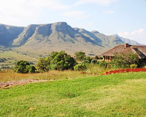 An exterior view of Verlorenkloof Estate resort unit alongside the meadow and mountains.