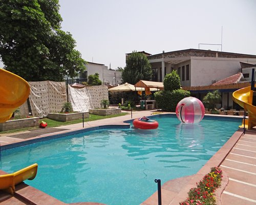 An outdoor swimming pool with water slider alongside resort unit.