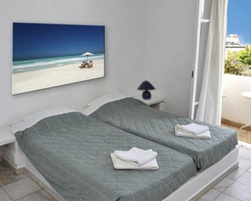 A well furnished bedroom with twin beds and balcony.