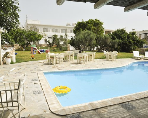 An outdoor swimming pool with chaise lounge chairs and patio alongside resort units.