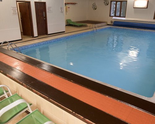 An indoor swimming pool with chaise lounge chairs.