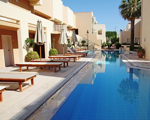 An outdoor swimming pool with chaise lounge chairs and thatched sunshades alongside multi story resort units.