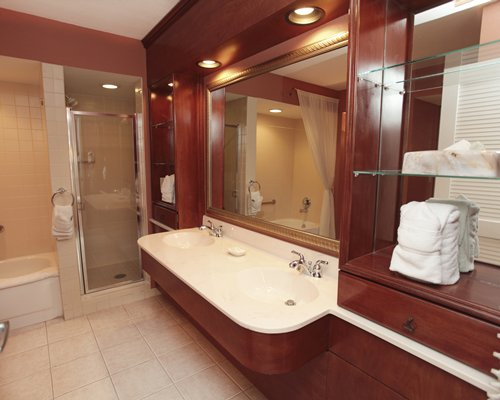 A bathroom with a shower stall double sink mirror bathtub and shower.