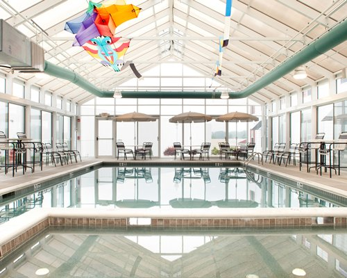 An indoor swimming pool with patio sunshades and an outside view.