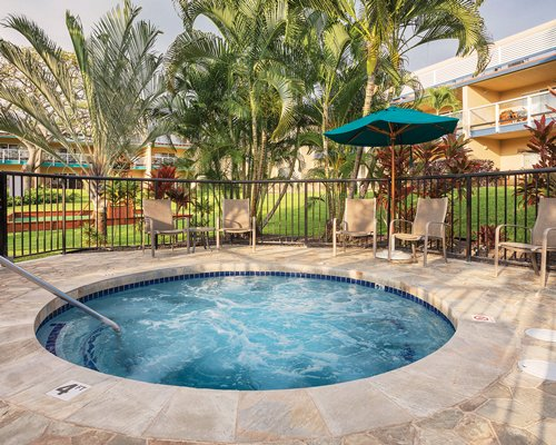 An outdoor hot tub with patio furniture and sunshades.