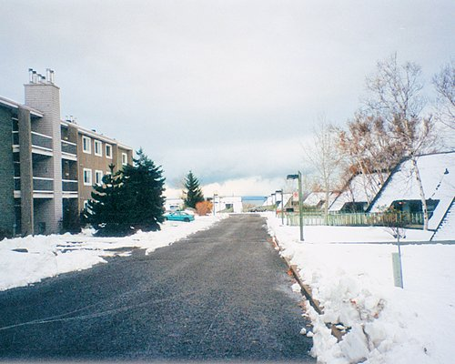 A street view of multi story resort units covered in snow.