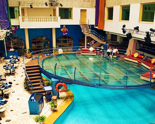 A large indoor swimming pool with patio furniture alongside the resort.