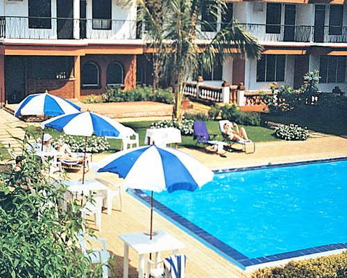 An outdoor swimming pool with chaise lounge chairs and patio furniture alongside resort units.