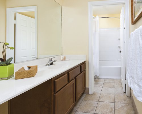 A bathroom with bathtub shower and single sink vanity.