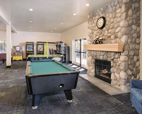 Indoor recreation room with arcade games air hockey pool table fire in the fireplace and outside view.