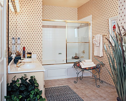 A bathroom with shower bathtub and double sink vanity.