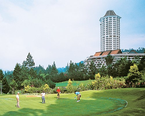 A golf course surrounded by wooded area alongside the skyscraper.