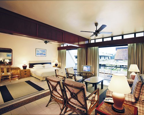 A well furnished bedroom with living area television and balcony.
