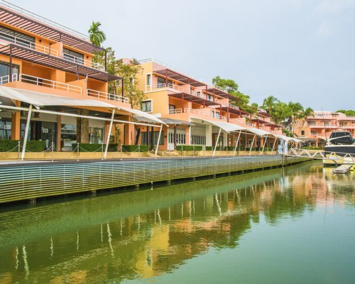 An exterior view of multi story resort units with a waterfront.