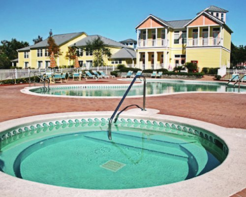 An outdoor swimming pool with hot tub with chaise lounge chairs alongside the resort unit.