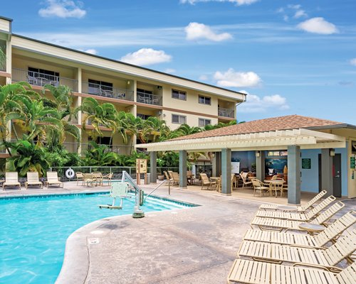 An outdoor swimming pool with chaise lounge chairs and poolside bar alongside the resort unit.