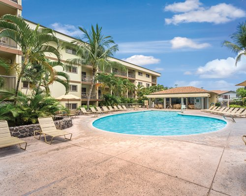 Scenic exterior view of WorldMark Kona with outdoor swimming pool and chaise lounge chairs.