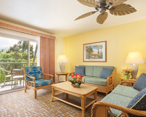 A well furnished living room with a balcony and patio furniture.