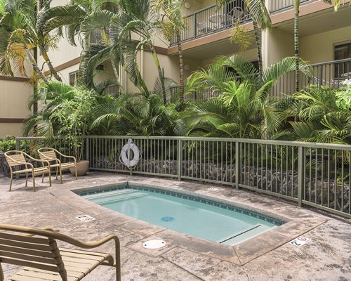 An outdoor hot tub with patio furniture alongside multi story units.