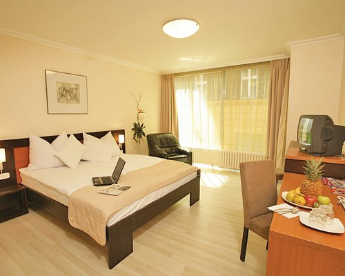 A well furnished bedroom with a television and laptop on the bed.