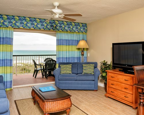 A well furnished living room with television balcony patio chairs and waterfront view.