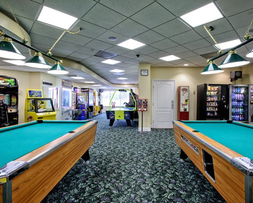 Indoor recreation room with pool tables air hockey and arcade games.