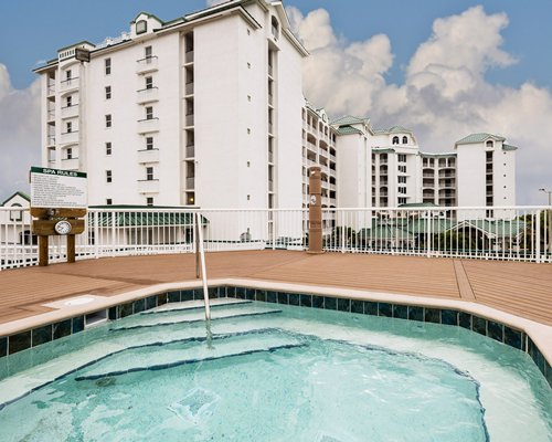 Outdoor hot tub alongside multiple unit balconies.