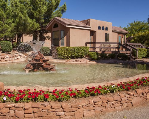 Exterior view of Sedona Pines Resort with grotto pool and fountain.