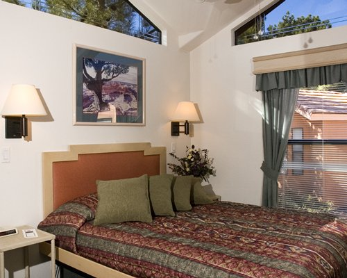 A well furnished bedroom and an outside view.