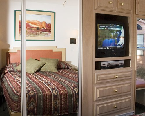A well furnished bedroom with a television.