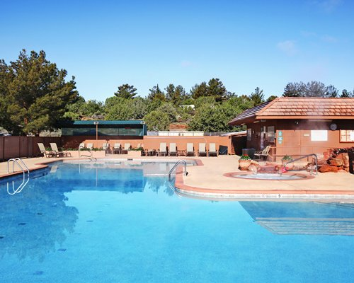 Large outdoor swimming pool with a hot tub and chaise lounge chairs surrounded by wooded area.