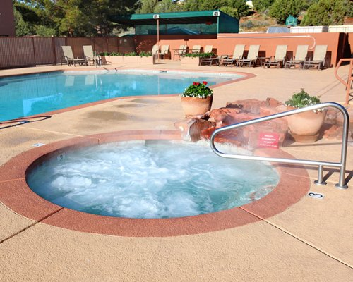 An outdoor hot tub alongside swimming pool.