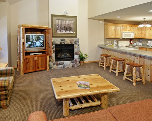 An open plan living room with television fire in the fireplace and kitchen with breakfast bar.