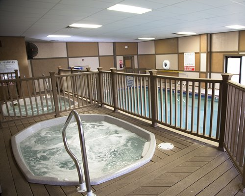 An indoor hot tub alongside swimming pool.