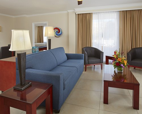 A well furnished living room with queen bed television balcony patio chairs and ocean view.