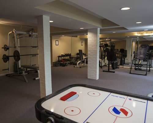 A well equipped indoor fitness center with an air hockey table.