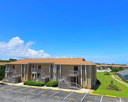 An outdoor swimming pool with chaise lounge chairs alongside resort units.