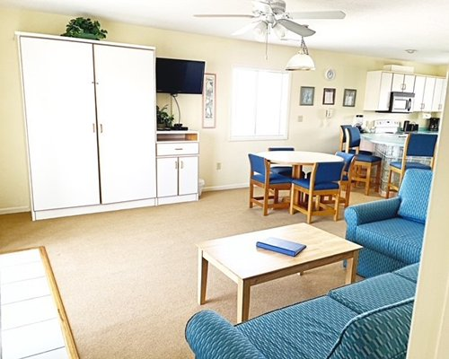 A well furnished dining area alongside a kitchen with a breakfast bar.
