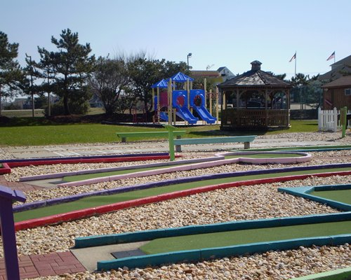 Scenic view of putt putt golf course alongside patio and kids playscape.