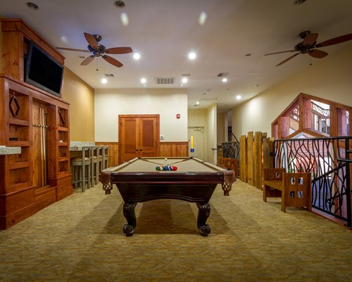 An indoor recreation room with pool table and television.