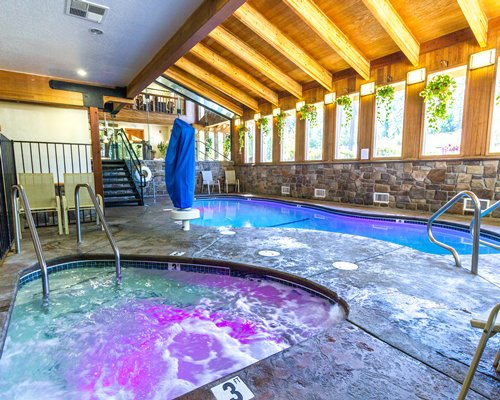 An indoor swimming pool with hot tub and patio alongside stairway.