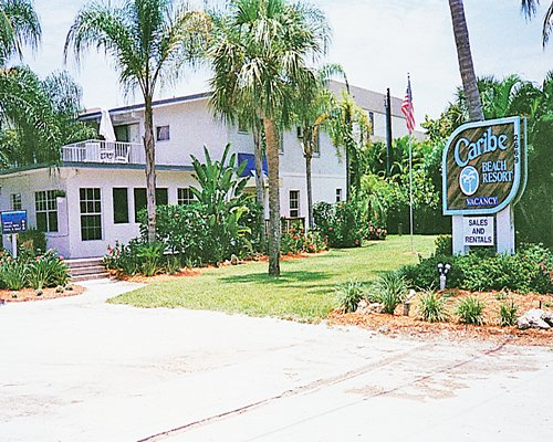 An exterior view of the Caribe Beach Resort and the signboard.