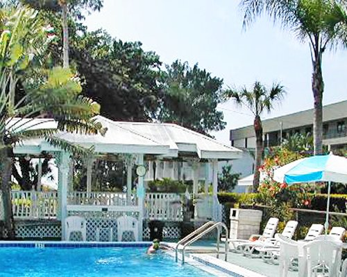 An outdoor swimming pool with a chaise lounge chairs and sunshades alongside resort.