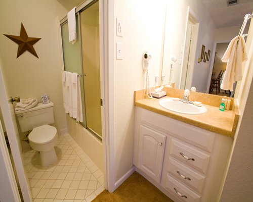A bathroom with shower sink and vanity.