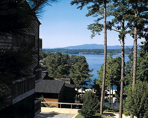 An exterior view of the resort with waterfront surrounded by trees.