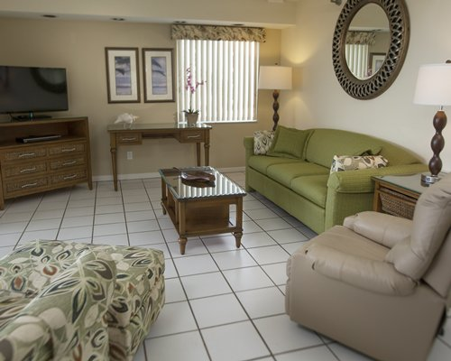 A well furnished living room with queen pull out sofa and a television.