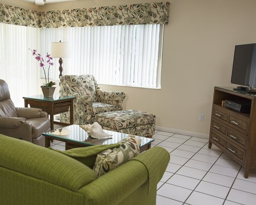 A well furnished living room with a television and sofas.