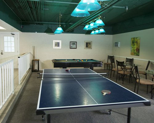 An indoor recreation room with ping pong and pool table.