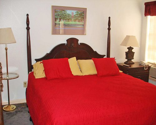 A well furnished bedroom with queen bed and two lamps.